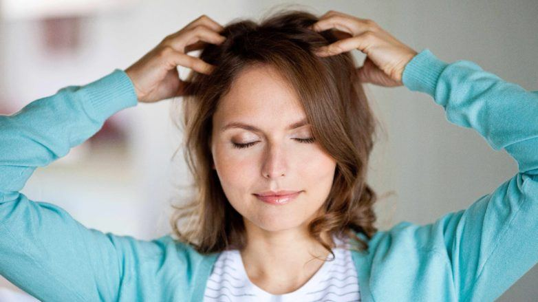 Dry scalp treatment guide: Woman with dark brown wavy medium-length hair, touching her scalp, wearing blue cardigan with white top