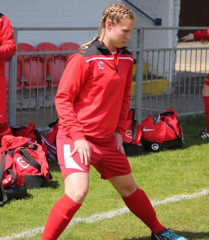 Working It: woman with blonde dutch boxer braids hairstyle wearing red football kit.