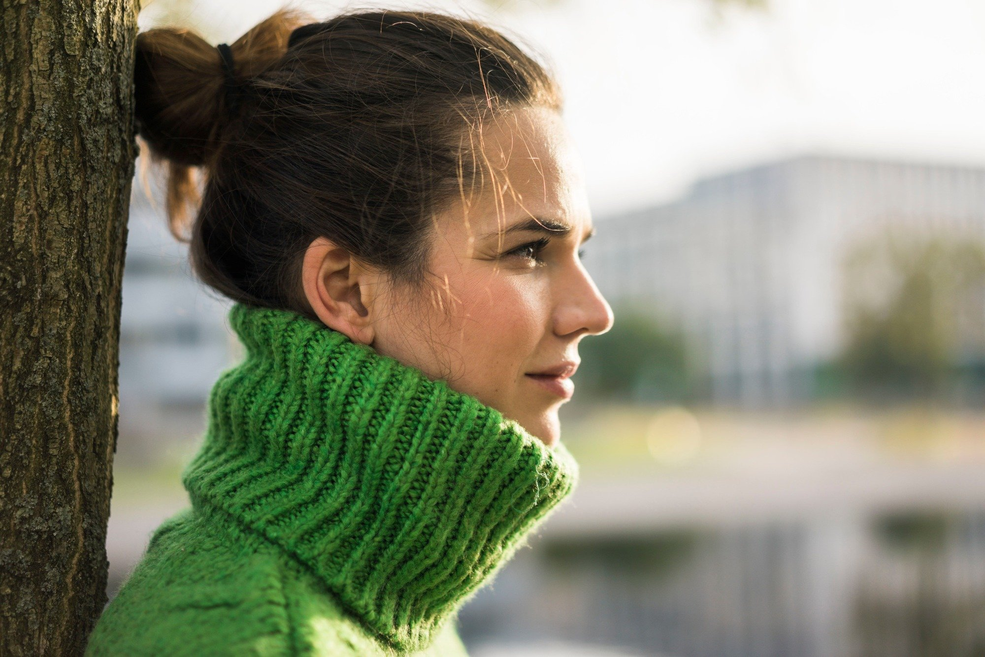 School Run Hairstyles: Shot of woman with dark brown hair styled into a knot bun hairstyle, wearing green turtleneck