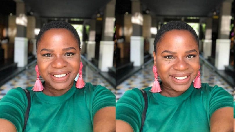 Real Hair Stories Nadia Williams: Young black woman with shaved hairstyles wearing a green top and statement earrings