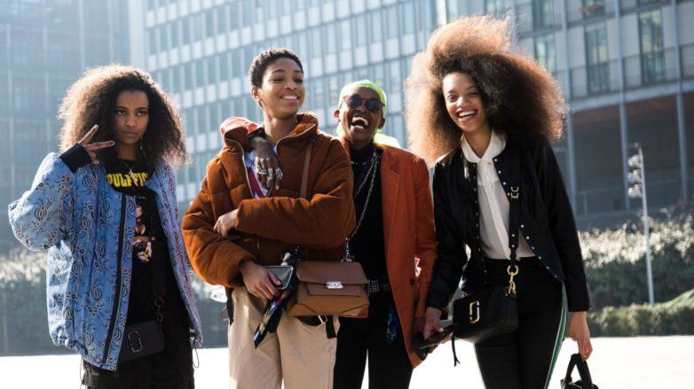Group shot of women with natural hair laughing and posing outside a building