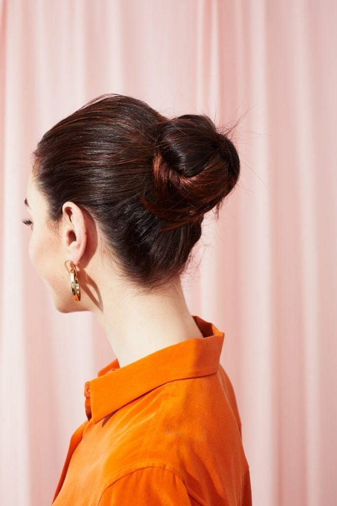Woman with dark brown hair styled into a bun updo