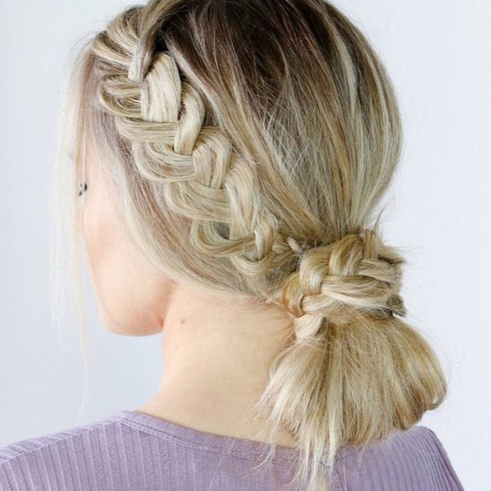 Blonde woman with straight hair in a low bun with side braid