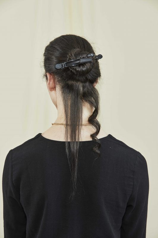 woman with sectioned off dark brown hair ready to be curled