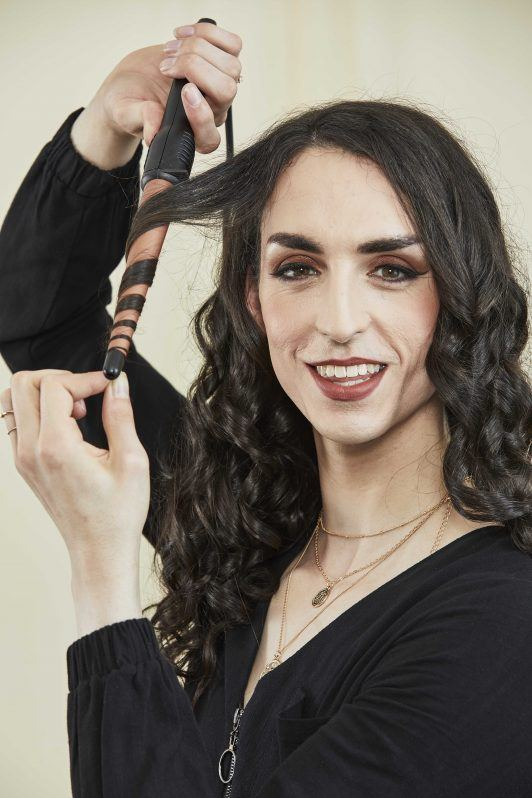 woman using a curling wand to curl her hair