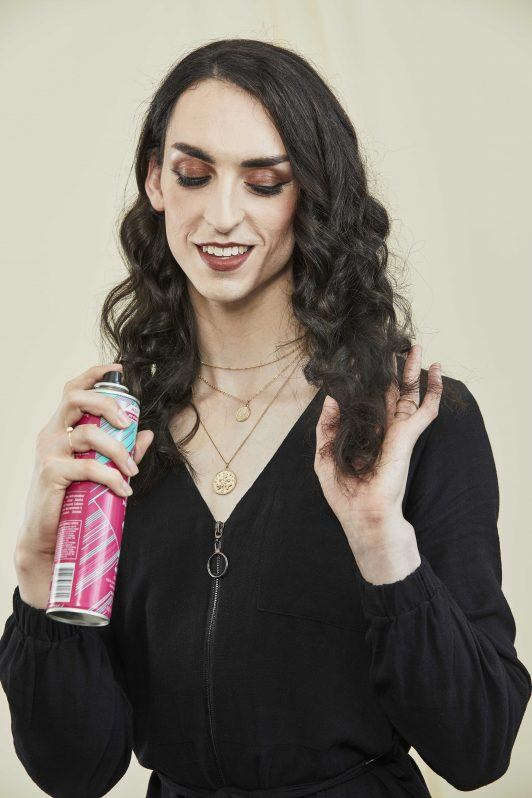 woman with with dark curly hair spraying hairspray into her hair