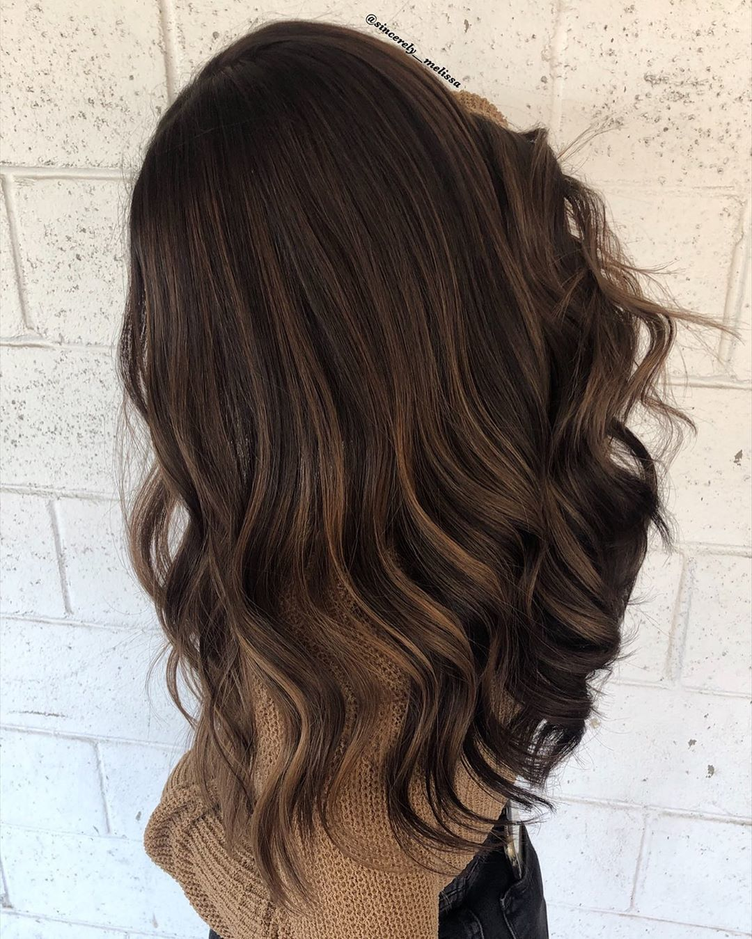 Woman with dark long hair with cocoa brown subtle highlights in her hair