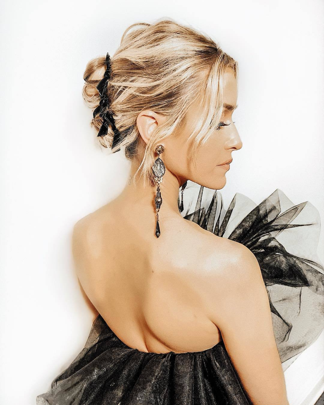 Wedding hairstyles: Side shot of woman with bronde blonde hair styled into a French twist updo with velvet bows, wearing statement earrings and black dress