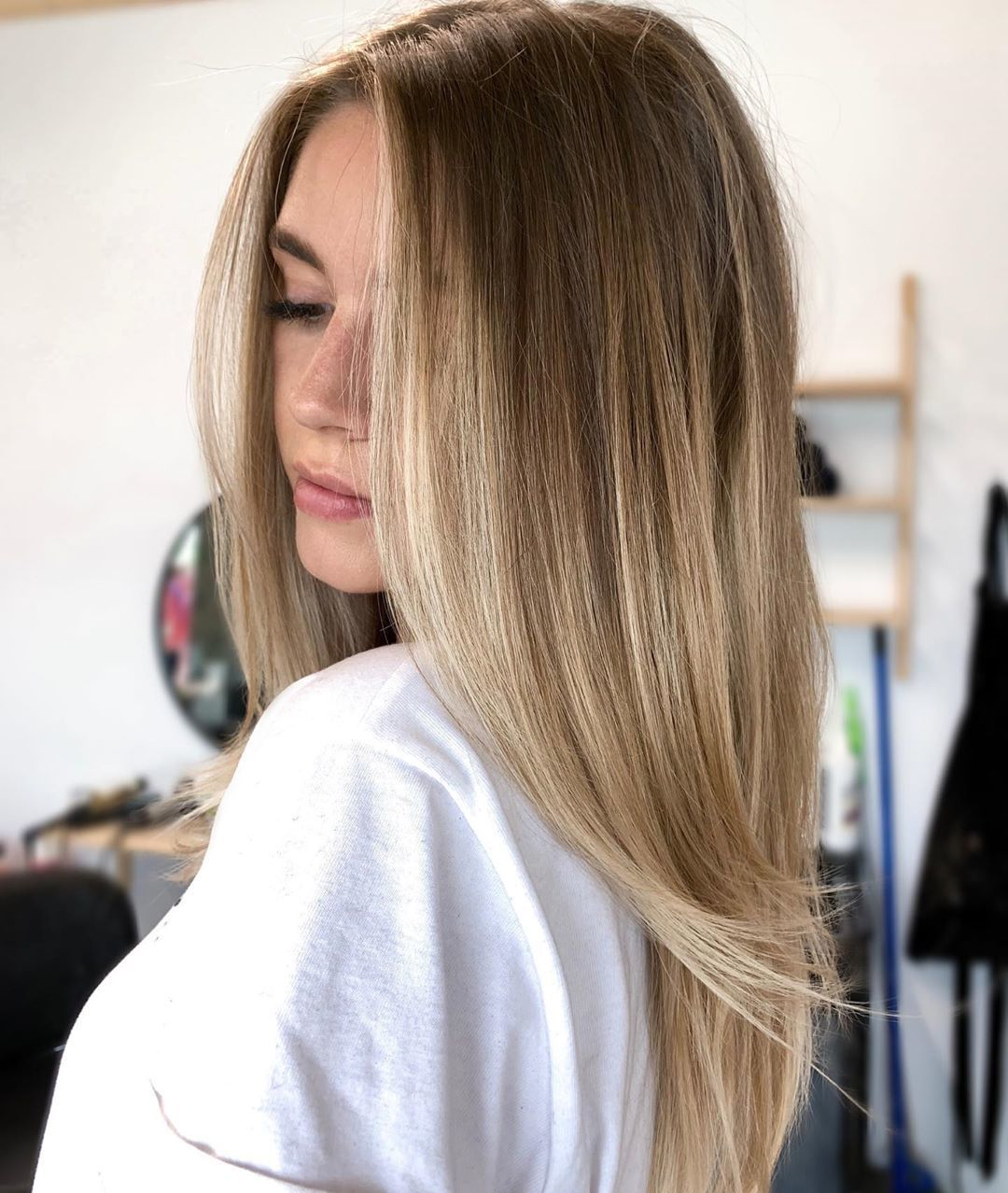 Woman with blown out, long light brown hair with golden balayage hair colour