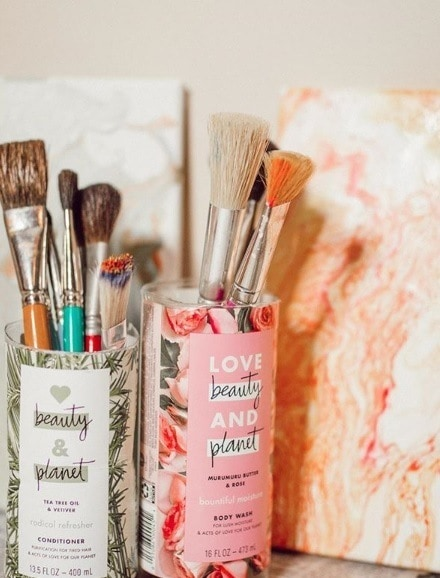 Close-up photo of upcycled Love Beauty And Planet shampoo bottles being used as a paintbrush holder