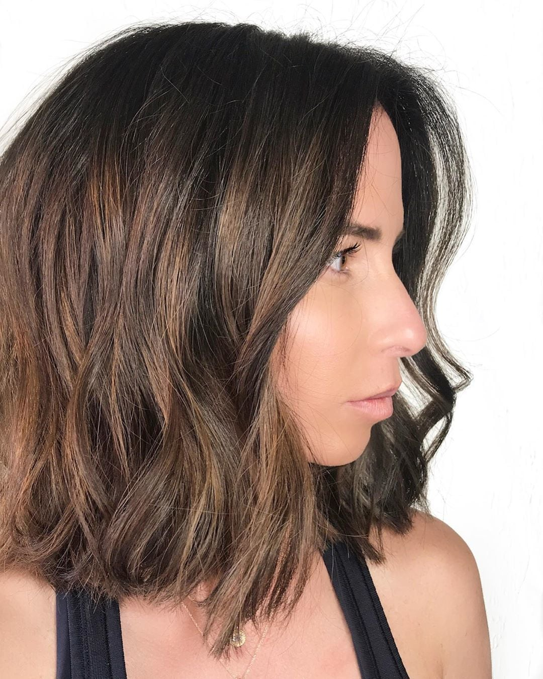 Woman with long bob haircut with light chocolate balayage highlights in it