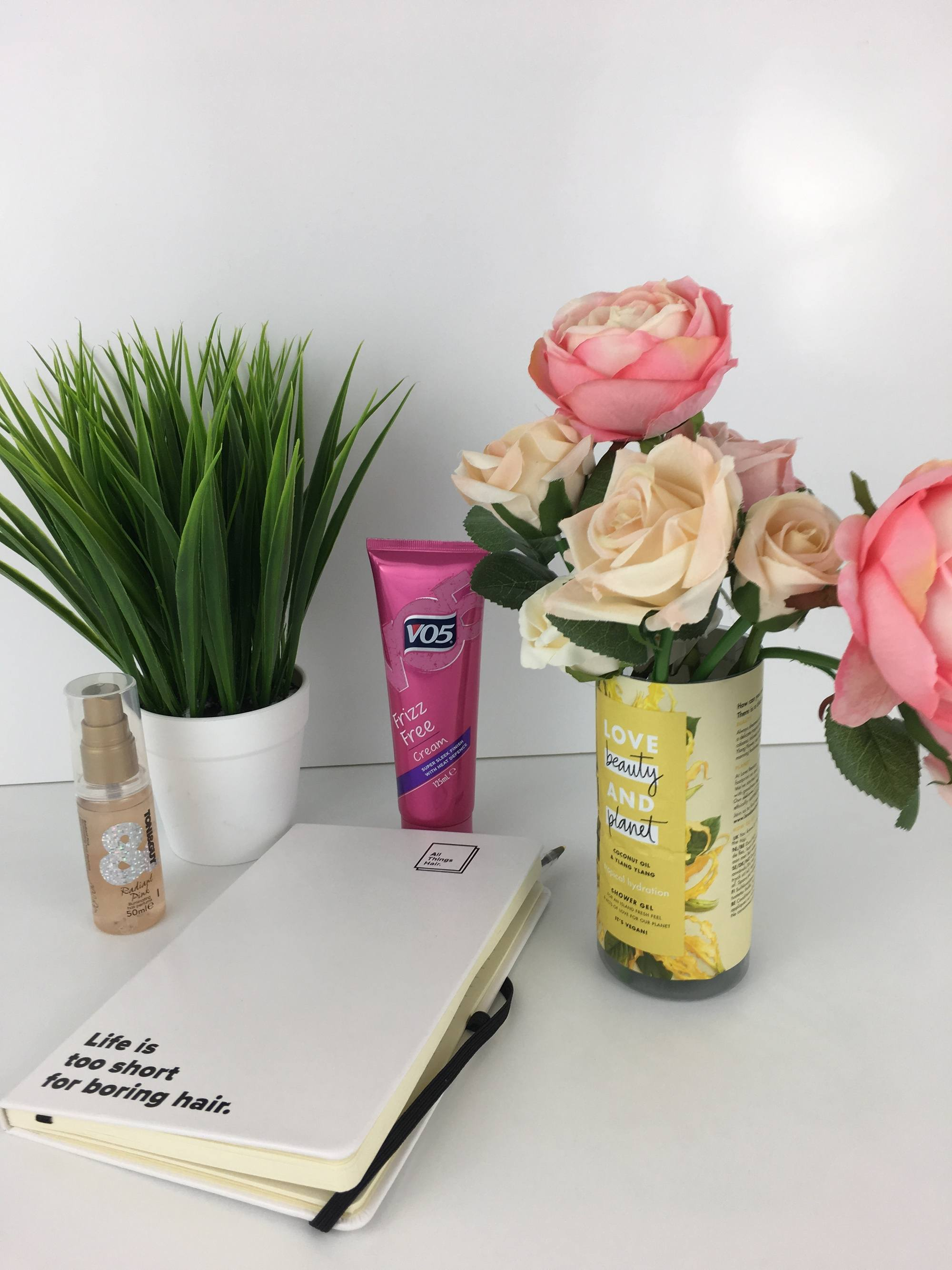 World Earth Day: Picture of plastic bottle with flowers in it, with a notebook and plant on the desk