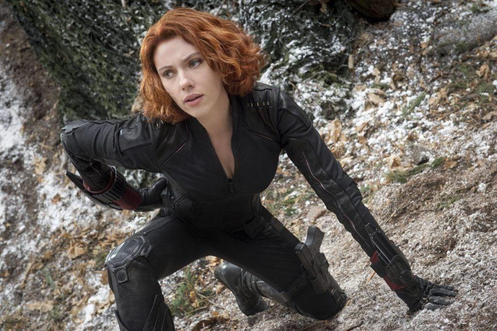 Marvel hairstyles: Scarlett Johansson with short wavy copper red bob wearing black jumpsuit.