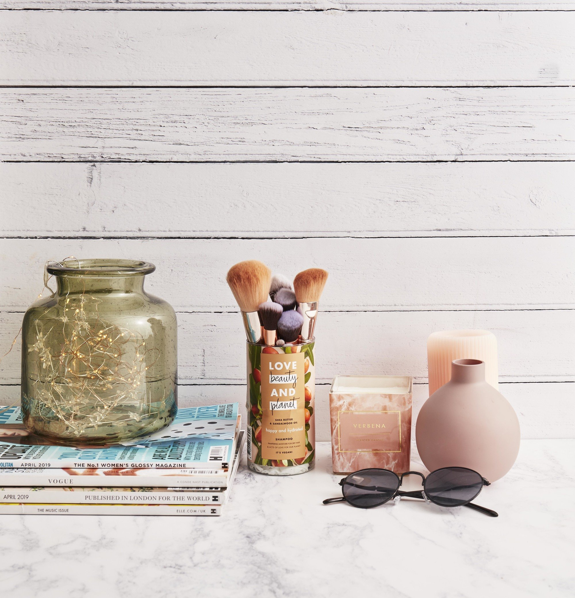 Flatlay photo of an upcycled Love Beauty And Planet shampoo bottle being used as a makeup brush holder, with vases, candles, magazines and sunglasses
