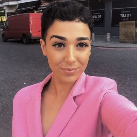 Real Hair Stories Yasmin Ajaj with a short dark brunette curly pixie cut, wearing a pink blazer