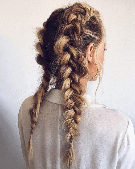 Woman with long dark blonde hair in double dutch braids