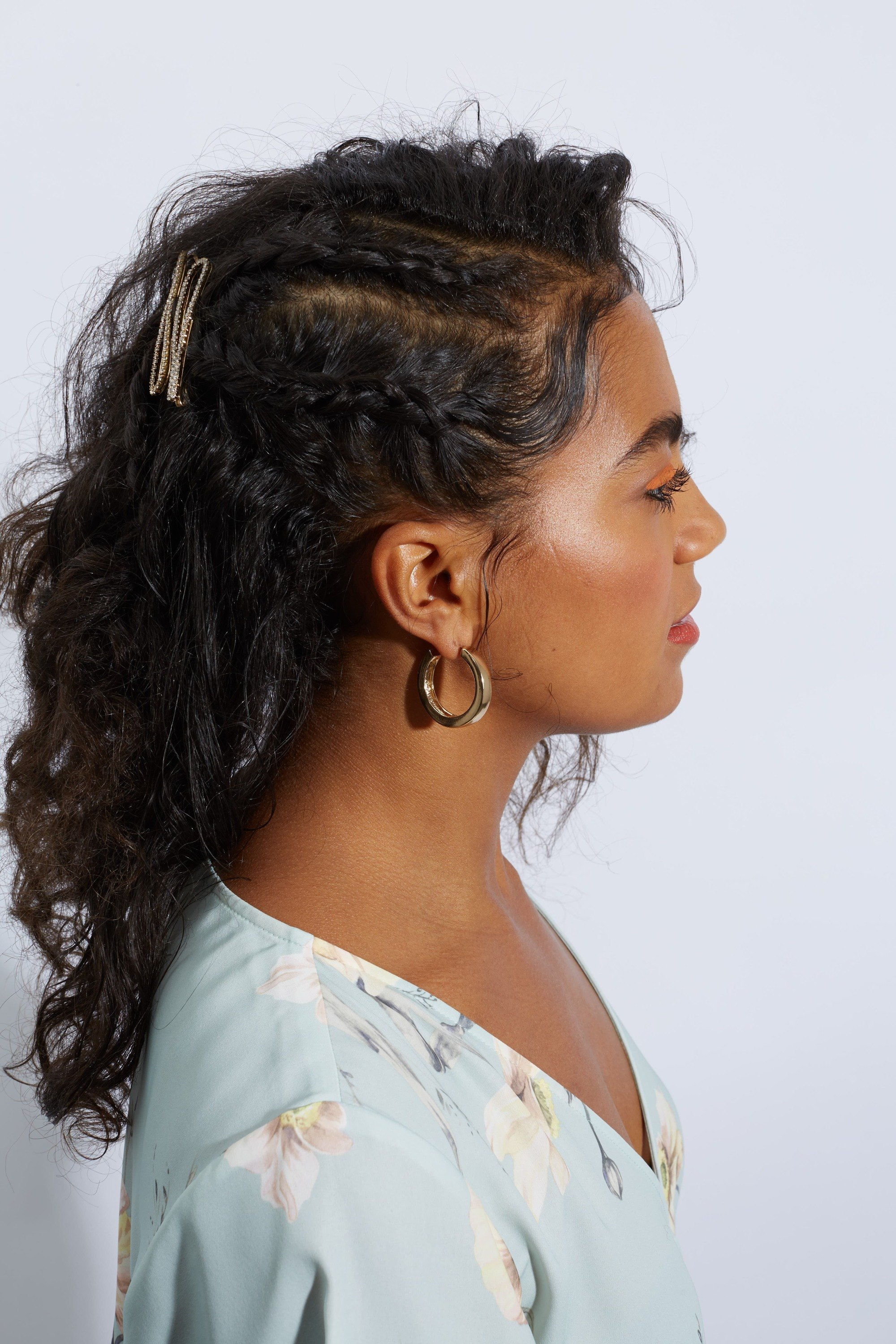 Bridesmaid hairstyles: Woman with loose naturally curly hair styled into half side braids with clips, wearing hoops and floral dress