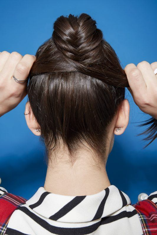 Brunette woman doing a fishtail braid ponytail.