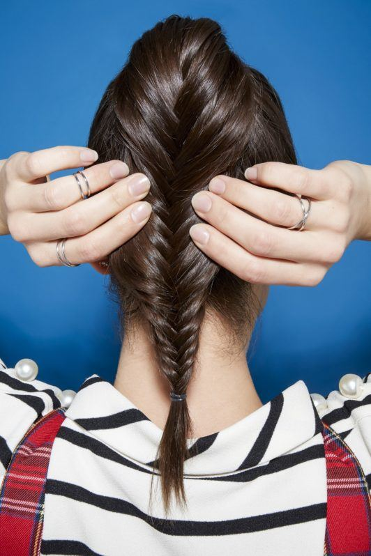 Brunette woman pancaking a fishtail braid ponytail