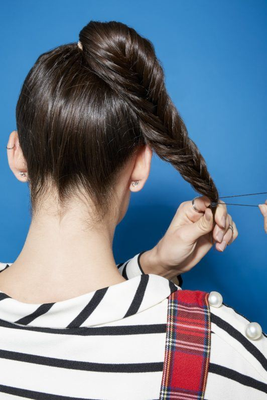Brunette woman securing her fishtail braid ponytail