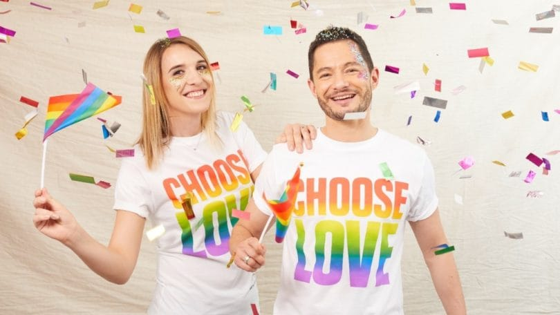 Blonde woman and brown haired man wearing Pride tshirts and waving rainbow flags with confetti