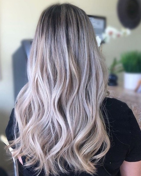 Woman with long wavy ash blonde balayage hair