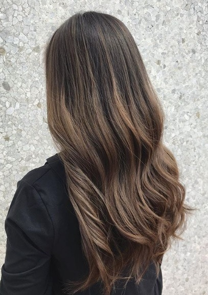 Woman with long ash brown balayage wavy hair