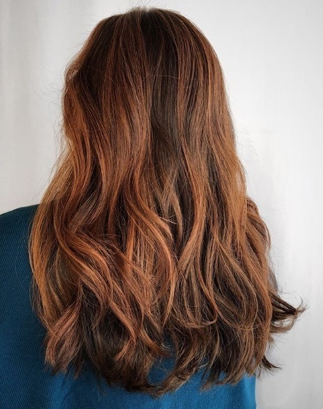 Woman with mid length auburn balayage hair