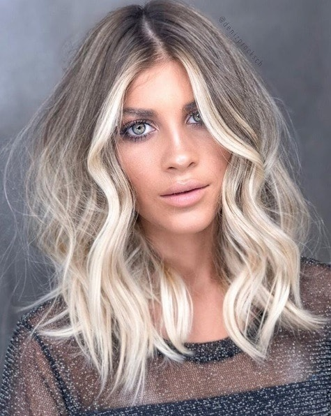 Woman with a wavy ashy blonde balayage lob