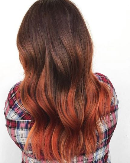 Woman with long wavy black and orange ombre hair