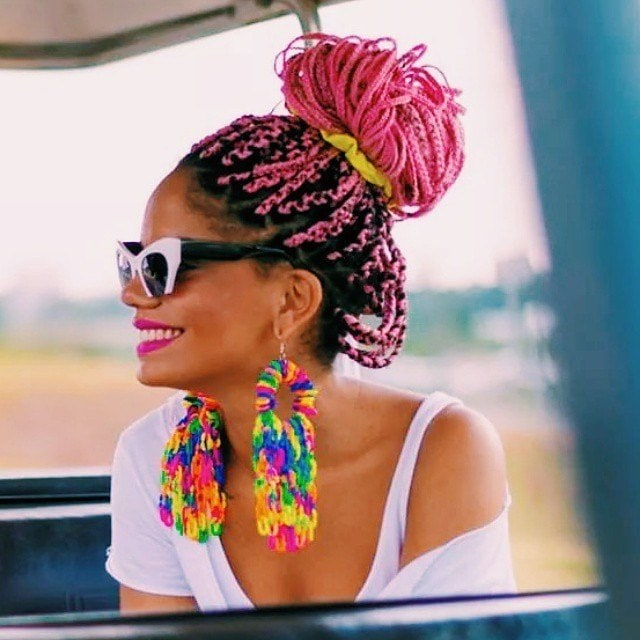 woman with pink box braids styled into a messy high bun