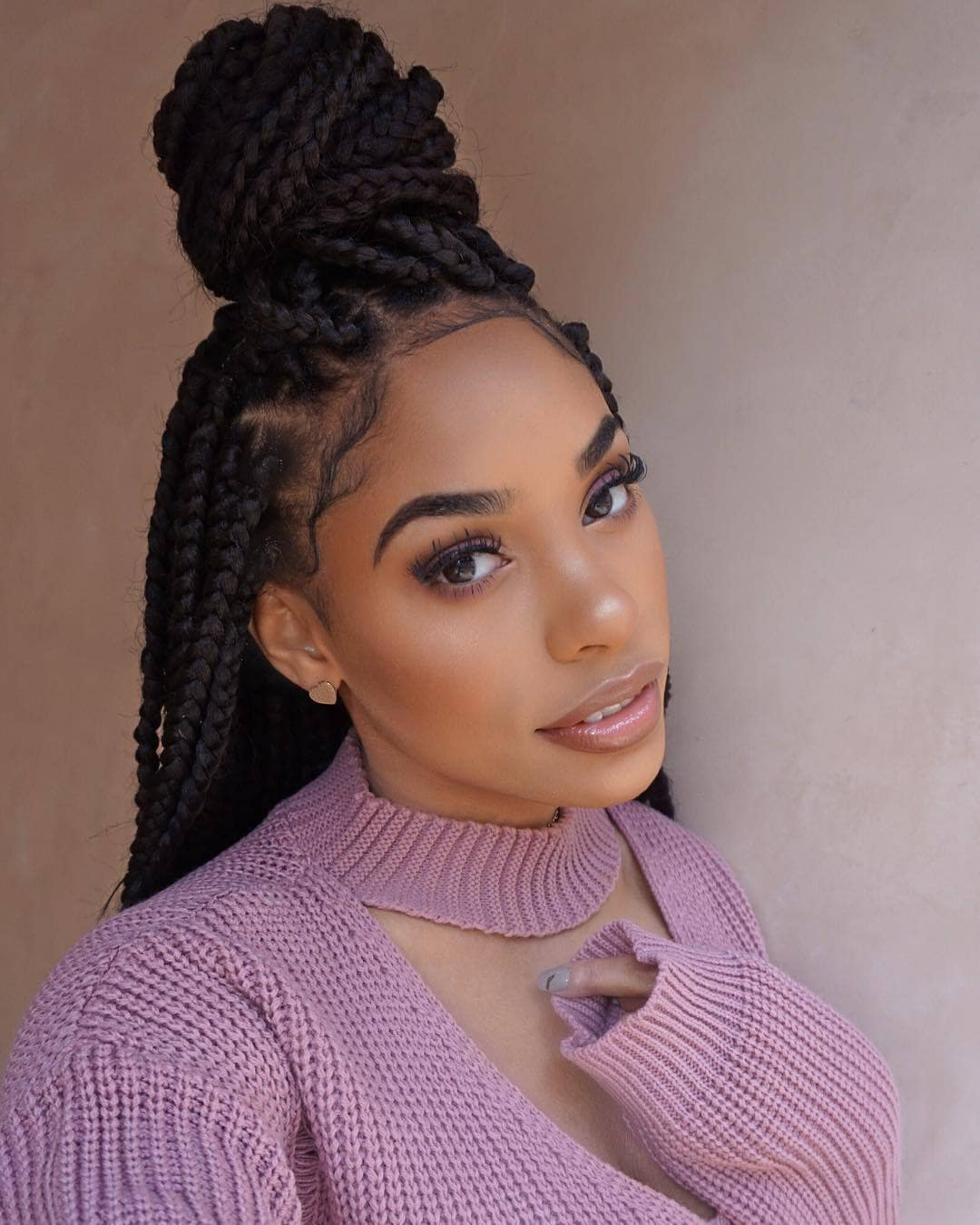 woman with thick box braids styled into half-up, half-down style