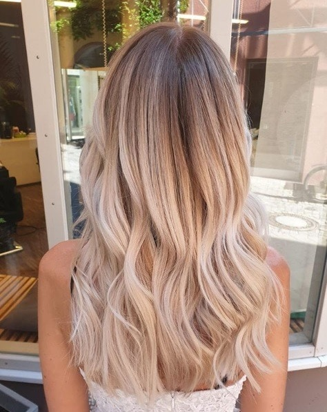 Woman with long wavy light blonde balayage hair