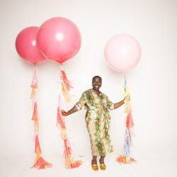 A black woman happily laughing while holding pastel pink balloons