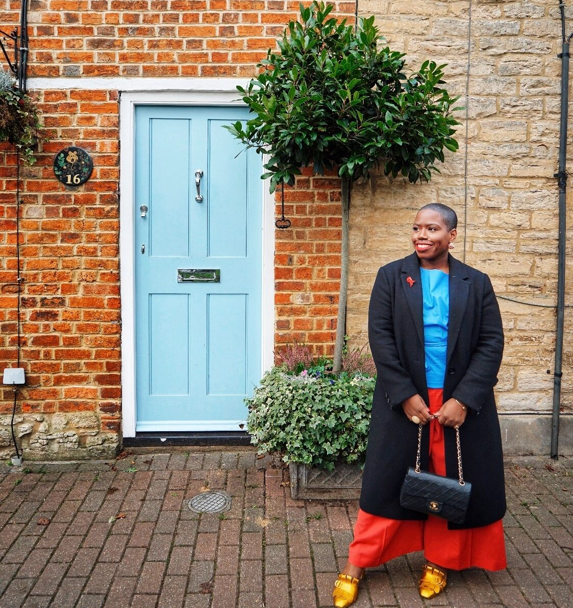 Black woman standing in front a pale blue door