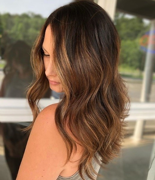 Woman with mid-length wavy caramel balayage hair