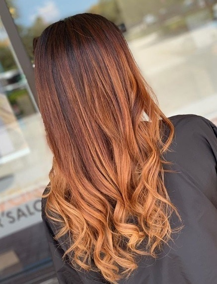 Woman with long curly copper balayage hair