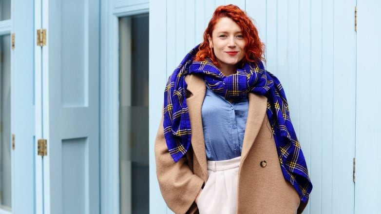 Rhyannon Styles with red curly hair wearing a large scarf