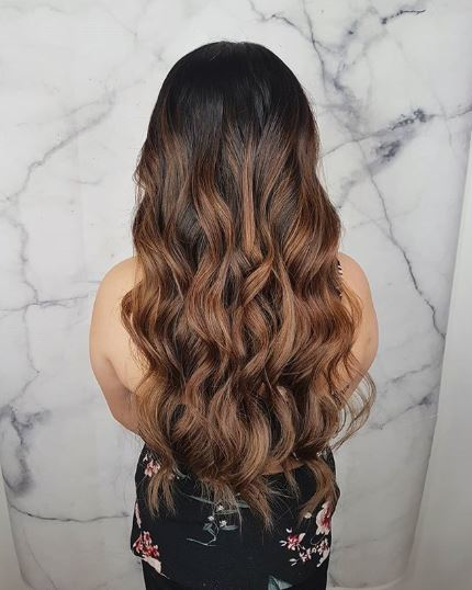 Woman with long wavy dark brown ombre hair