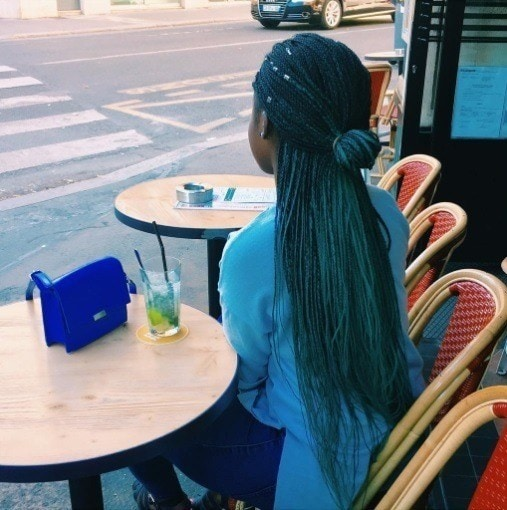 woman with blue skinny braids in a half-up bun