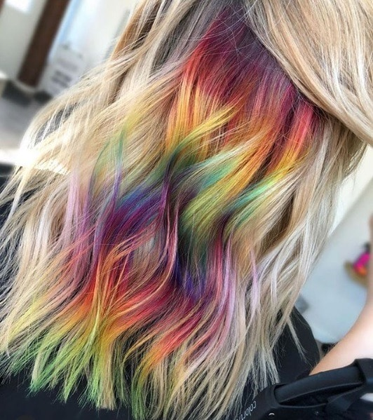 Woman with blonde wavy hair and hidden rainbow colour