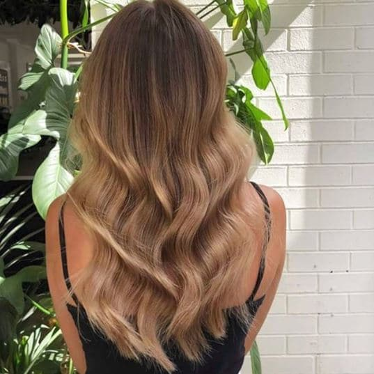 Woman with long light brown wavy ombre hair