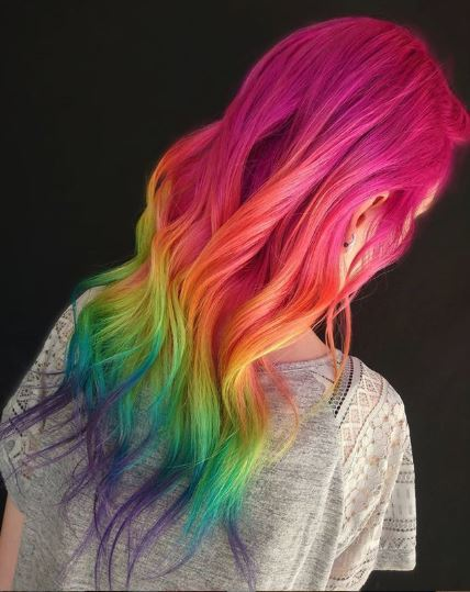 Woman with long wavy rainbow ombre hair
