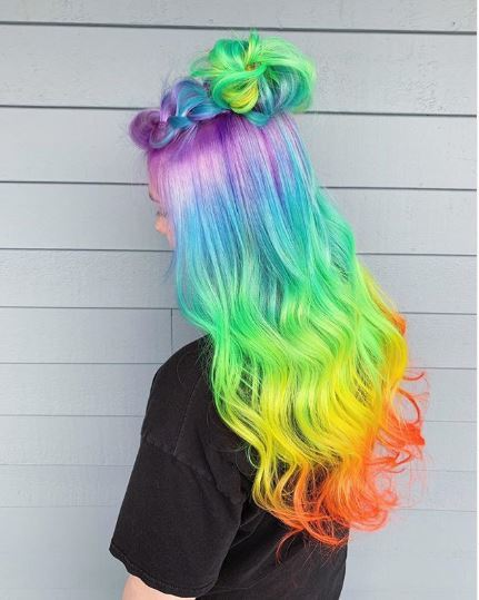 Woman with long neon rainbow hair in a braided half-up