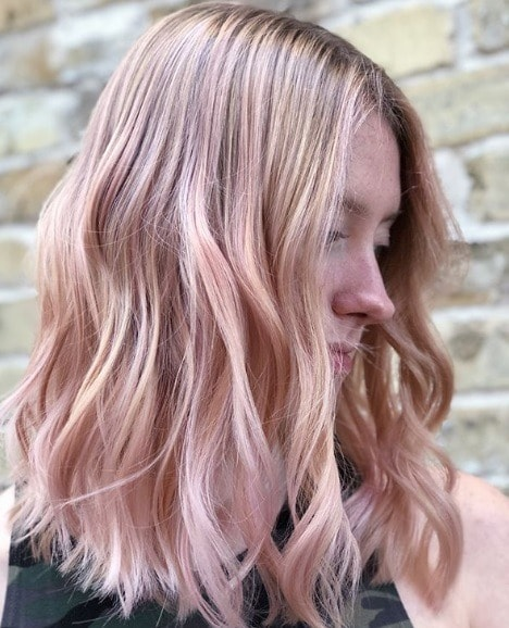 Woman with wavy shoulder length light pink balayage hair