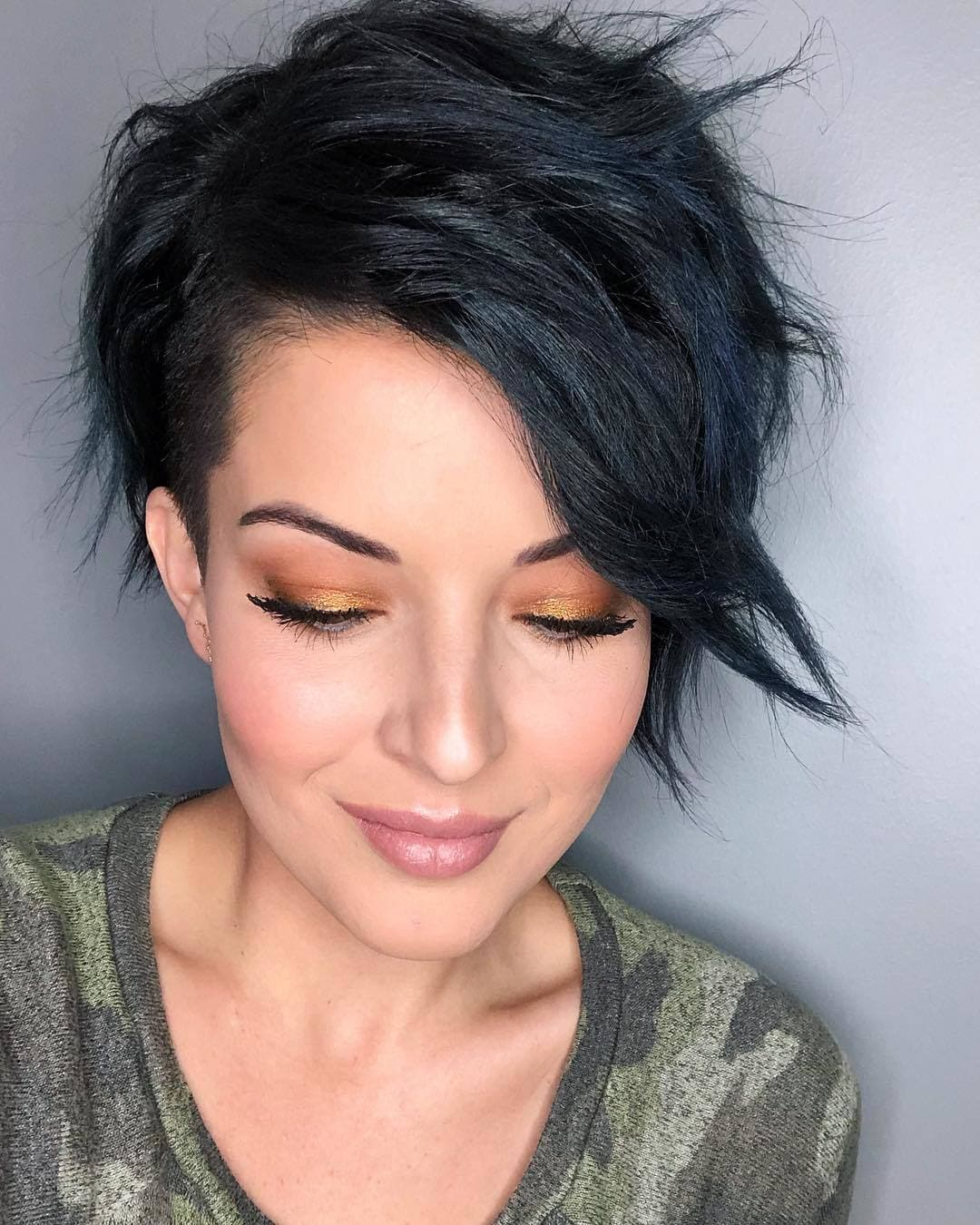 woman with dark brown side swept long bangs and pixie cut