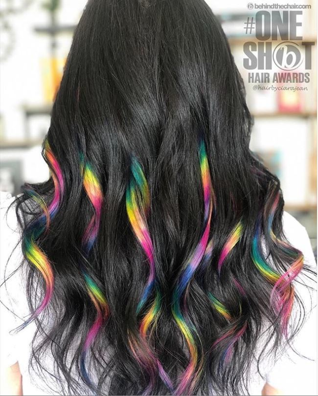Woman with dark brown wavy hair and rainbow highlights