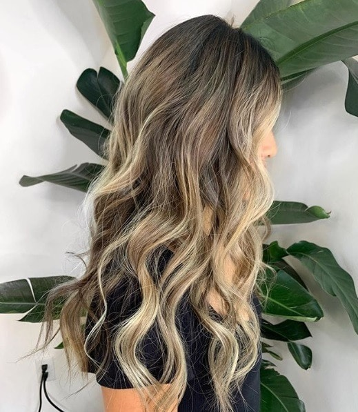 Woman with long curly blonde reverse balayage