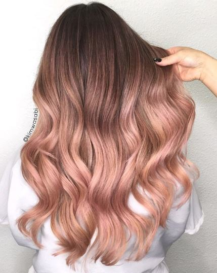 Woman with rose gold wavy ombre hair