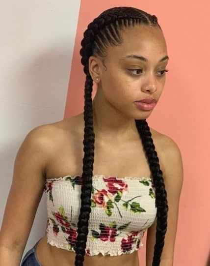Woman with dark brunette long hair styled in two cornrow braids